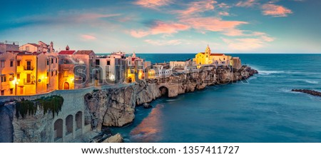 Exotic evening cityscape of Vieste - coastal town in Gargano National Park, Italy, Europe. Coloful spring sunset on Adriatic sea. Traveling concept background. #1357411727