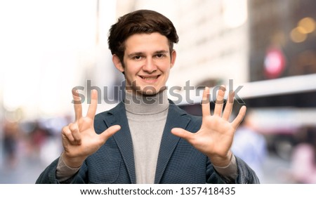 Teenager man with turtleneck counting eight with fingers at outdoors #1357418435