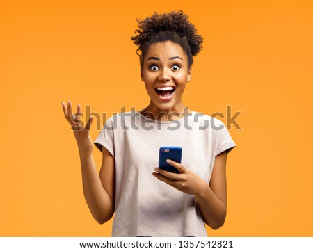 Amazed girl holds smartphone, happy to receive notification, gestures actively from happiness. Photo of african american girl on orange background. Emotions and pleasant feelings concept