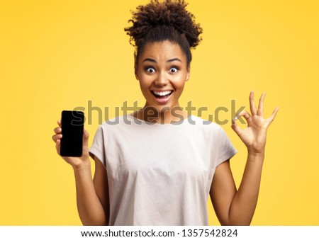 Overjoyed happy girl holds mobile phone and makes okay gesture. Photo of african american girl wears casual outfit on yellow background. Emotions and pleasant feelings concept. #1357542824