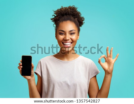 Happy girl holds mobile phone and makes okay gesture. Photo of african american girl wears casual outfit on turquoise background. Emotions and pleasant feelings concept.