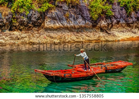 Unrecognizable vietnamese woman in conical hat rowing boats that bring tourists traveling inside limestone cave with limestone island in background in summer at Halong Bay. Quang Ninh, Vietnam. Royalty-Free Stock Photo #1357558805