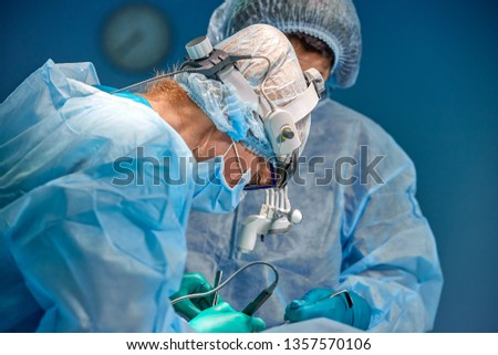 surgery, medicine and people concept - group of surgeons at operation in operating room at hospital #1357570106