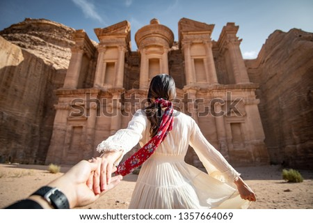 Asian woman tourist in white dress holding her couple hand at Ad Deir or El Deir, the monument carved out of rock in the ancient city of Petra, Jordan. Travel UNESCO World Heritage Site in Middle East #1357664069