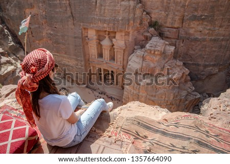 Asian woman traveler sitting on carpet viewpoint in Petra ancient city looking at the Treasury or Al-khazneh, famous travel destination of Jordan and one of seven wonders. UNESCO World Heritage site. #1357664090