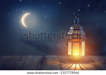 Ornamental Arabic lantern with burning candle glowing at night. Festive greeting card, invitation for Muslim holy month Ramadan Kareem. #1357778966