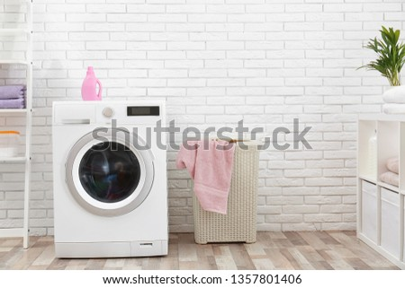 Modern washing machine near brick wall in laundry room interior, space for text #1357801406