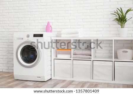 Modern washing machine near brick wall in laundry room interior #1357801409