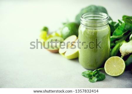 Glass jar mugs with green health smoothie, kale leaves, lime, apple, kiwi, grapes, banana, avocado, lettuce. Copy space, sunlight effect. Raw, vegan, vegetarian, detox, alkaline food concept #1357832414