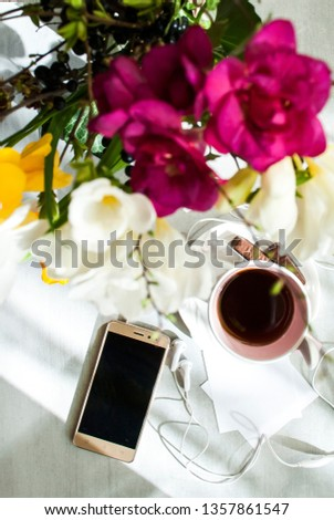 Concept of female good morning. Pink cup of tea or coffee, on a plate of candy, a smartphone, headphones, sheets for writing, a bouquet of flowers. Light background. Selective focus.