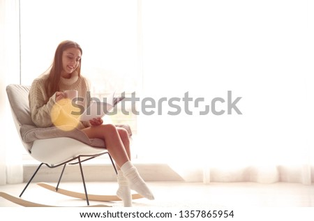Young woman with cup of coffee reading book near window at home, space for text #1357865954