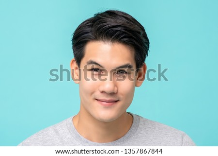 Smiling young handsome Asian man face studio shot isolated on light blue background