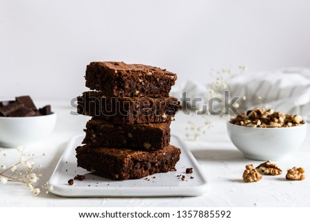 Homemade dark chocolate brownies on white table. Delicious bitter sweet and fudge. Chocolate cake #1357885592