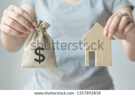 Hand holding money bag and wood house model.Saving money concept,new home in a housing development or community, #1357892858
