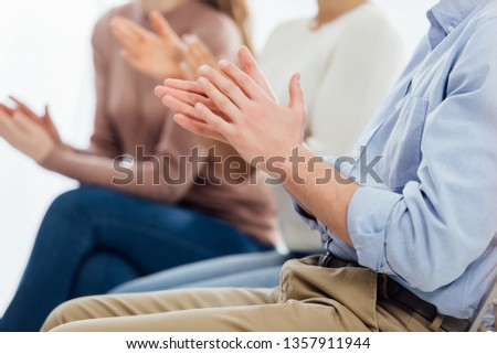 cropped view of people sitting and applauding during group therapy session #1357911944