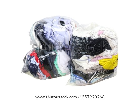 second hand clothes in the plastic bag isolated white background, clothes in bags plastic for donation, pile of dirty clothes, old cloth in plastic bag, clothes second hand for donate, clipping path #1357920266