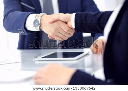 Group of business people or lawyers shaking hands finishing up a meeting , close-up. Success at negotiation and handshake concepts #1358069642
