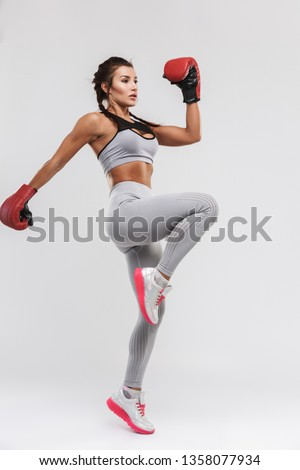 Picture of a beautiful young amazing strong sports fitness woman boxer posing isolated over white wall background make exercises with gloves.