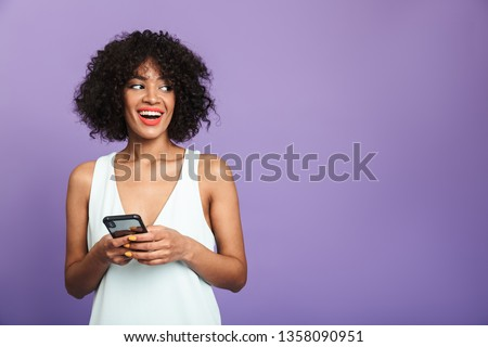 Happy pretty african woman holding smartphone and looking away over violet background #1358090951