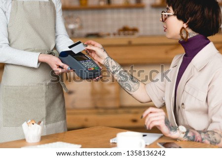 partial view of waitress holding payment terminal near businesswoman with credit card