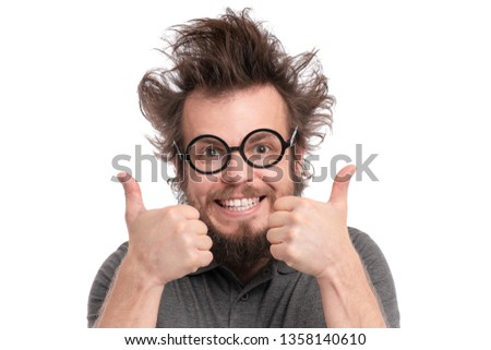 Crazy Bearded happy Man with funny Haircut in Eyeglasses making Thumbs up gesture. Cheerful and silly guy, isolated on white background. #1358140610