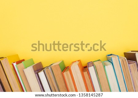 Bright colorful books with dark pages isolated on yellow #1358145287