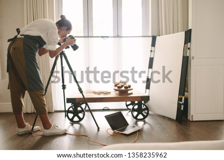 Professional food blogger taking pictures of pastry items on table with dslr camera. Female photographer taking pictures of sweet food, camera mounted on tripod with laptop on floor.