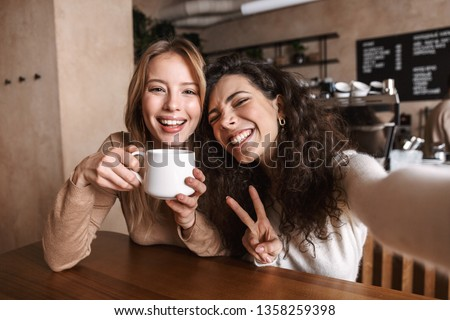 Image of excited happy pretty girls friends sitting in cafe take a selfie by camera. #1358259398