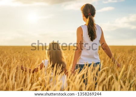 Young woman and her daughter walking on golden wheat field at sunny summer evening. #1358269244