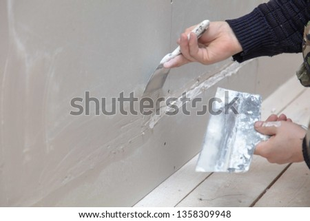 Worker aligns the walls with plaster. Repair in the house. #1358309948