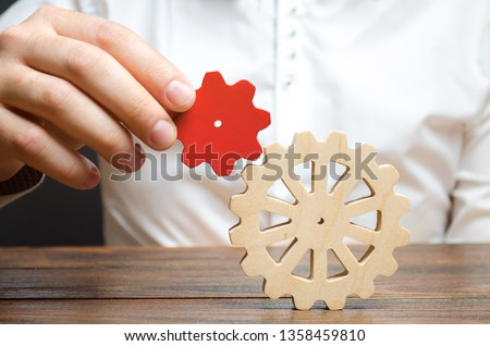 Businessman connects a small red gear to a large gear wheel. Symbolism of establishing business processes and communication. Increase efficiency and productivity. The best business formula for success #1358459810