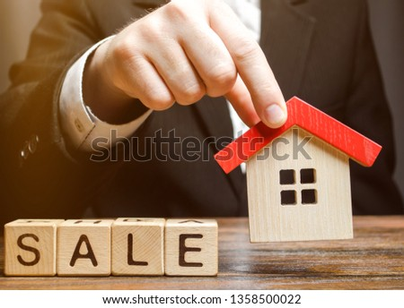 Wooden blocks with the word Sale and miniature house in the hands of a real estate agent. Real estate market. Selling a house, apartment. Trade of property. Affordable housing. Realtor #1358500022