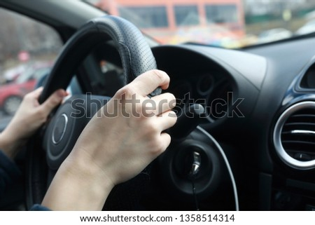 Hands of person on steering wheel of car #1358514314
