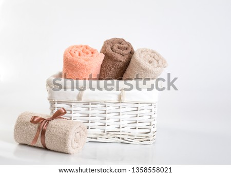 Rolled coral, beige and brown terry towels on a white background, rolled different colors terry towels with a ribbon against a white backdrop, towels in a white basket in front of a white  backdrop #1358558021