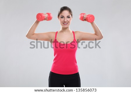Beautiful caucasian woman in fitness wear with dumbbells over background #135856073