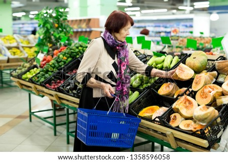 Grandma, the old woman chooses a pumpkin in the supermarket. #1358596058