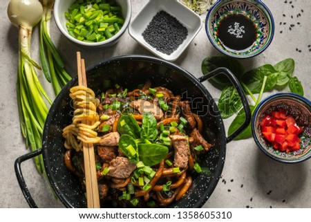 Chinese udon noodles with beef and vegatables fried in a pan on the gray table.  Top view #1358605310
