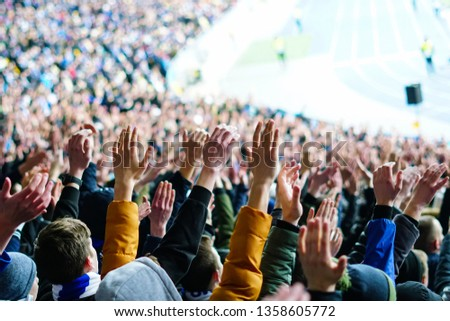 Vintage style photo of a crowd, happy people enjoying rock concert, raised up hands and clapping of pleasure, active night life concept #1358605772