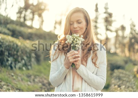 Happy woman with red long hair and a pleasant smile in the rays of the sun holds a bouquet of delicate flowers in front of her and enjoys #1358615999
