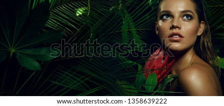 A beautiful tanned girl with natural make-up and wet hair stands in the jungle among exotic plants.fashion, beauty, makeup, cosmetics, beauty salon, style, personal care, posture, hair. #1358639222