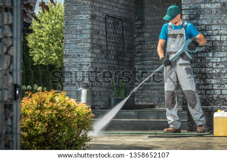 Driveway Pressure Washing. Caucasian Worker Cleaning Area in Front of the House. #1358652107