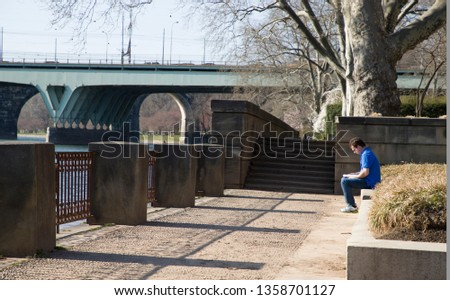 Philadelphia, PA / USA. April 3rd, 2019: White male in blue shirt sitting on stone ledge reading book by Schuylkill River in Philadelphia, PA in first warm day of Spring 2019.  #1358701127