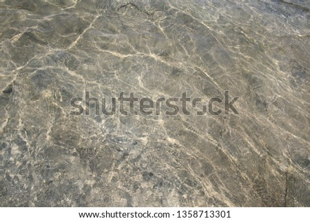 Water sun reflection of rock and sand texture #1358713301