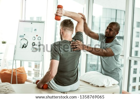 Medical support. Brunette man sitting on couch and doing exercises with dumbbells #1358769065