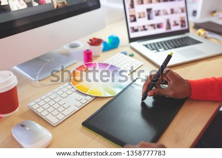 Close-up of young mixed-race female graphic designer using graphic tablet at desk in a modern office #1358777783
