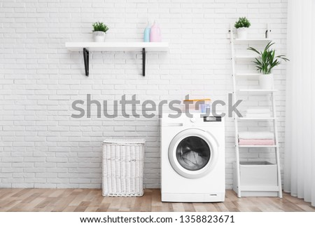 Modern washing machine near brick wall in laundry room interior, space for text #1358823671