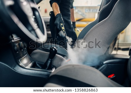 Carwash, worker cleans seats with steam cleaner Royalty-Free Stock Photo #1358826863