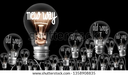 Large group of shining and dimmed light bulbs with fibers in a shape of New and Old Way words isolated on black background; concept of Innovation, Development and Success #1358908835