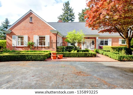 Brick red house with English garden and white window shutters. Summer landscape. #135893225