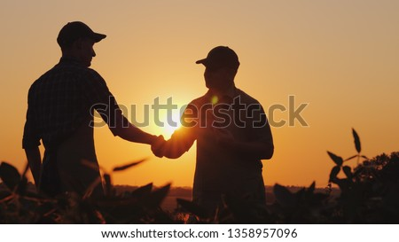 Two farmers talk on the field, then shake hands. Use a tablet #1358957096